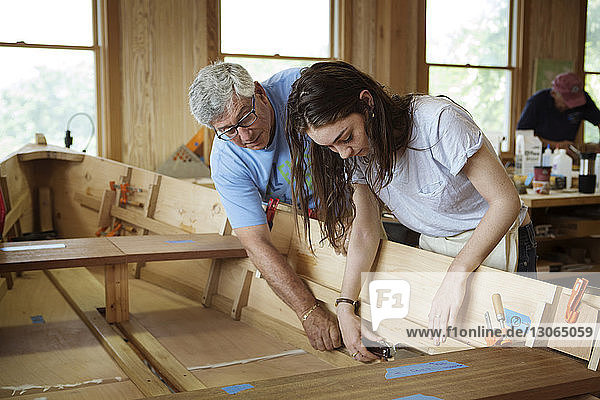 Senior man assisting woman while working on canoe in workshop
