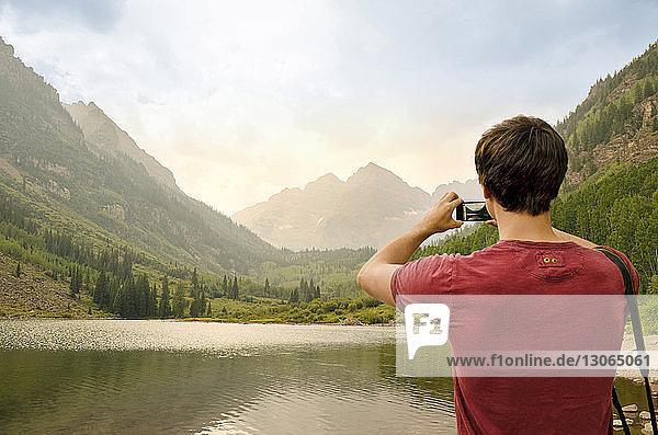 Rückansicht eines Mannes  der Berge fotografiert