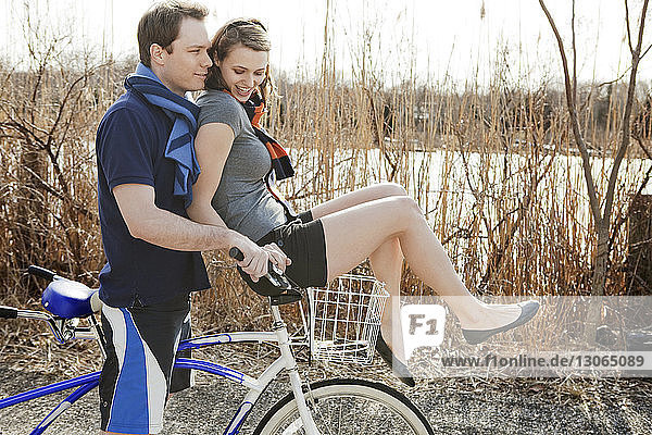 Woman sitting on handle of tandem bicycle by man at field