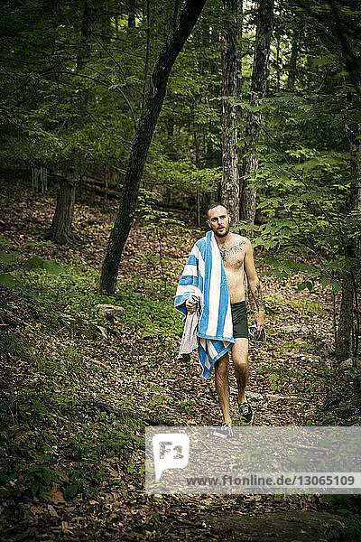 Shirtless man carrying towel and clothes while walking in forest