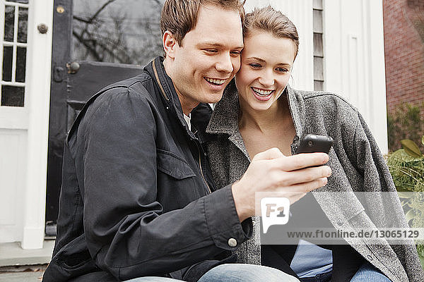 Couple looking at mobile phone while sitting outside house