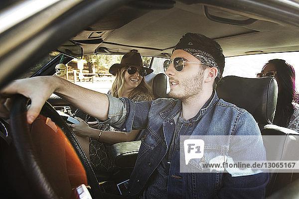 Glückliche Freunde im Auto sitzend