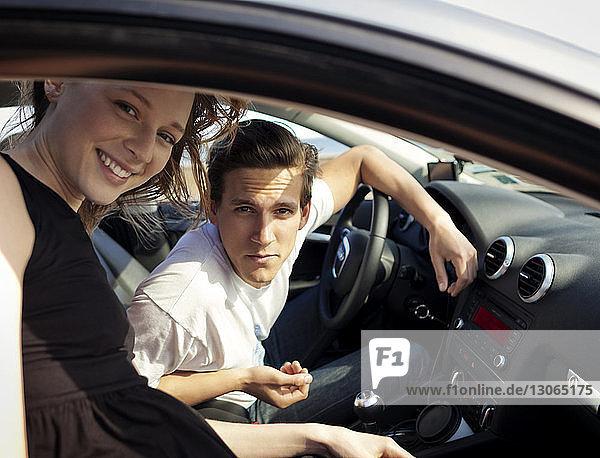 Porträt von Freunden  die durch das Fenster schauen  während sie im Auto sitzen