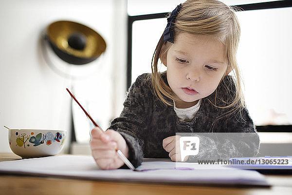 Mädchen malt  während sie zu Hause am Tisch sitzt