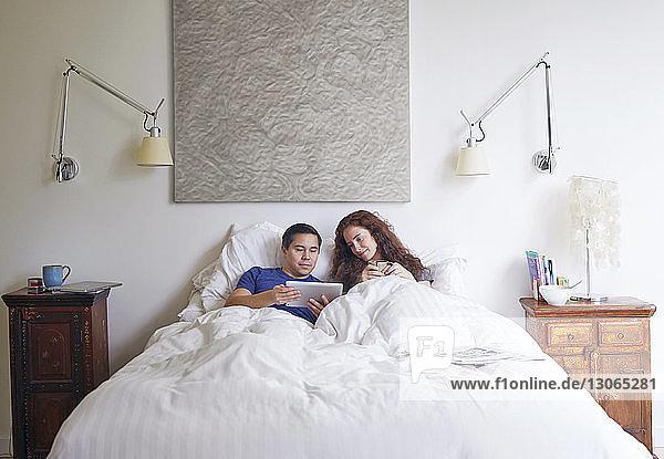 Ehepaar betrachtet Tablet-Computer  während es im Haus auf dem Bett liegt