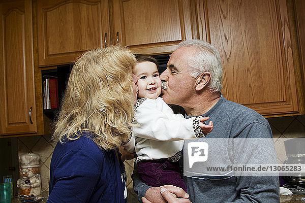 Großeltern küssen Kind  während sie in der Küche stehen