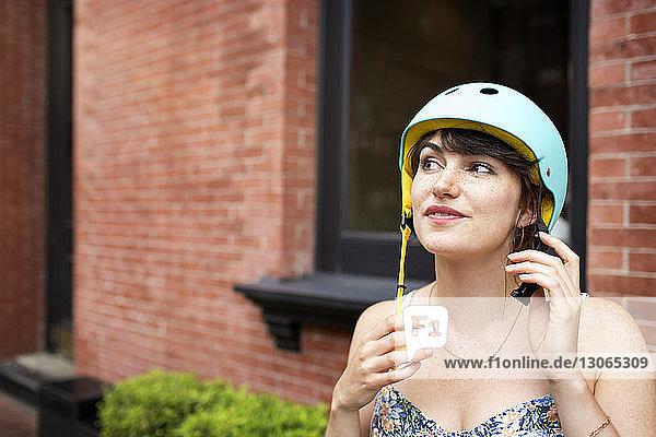 Frau schaut beim Tragen eines Fahrradhelms weg