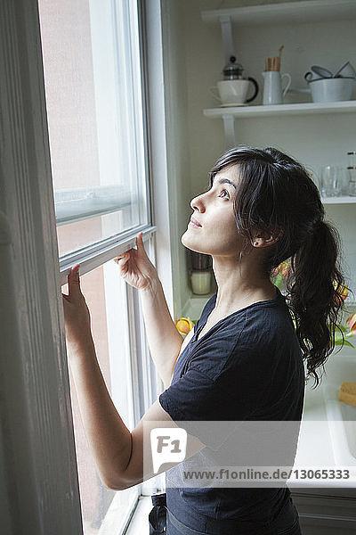 Seitenansicht der Frau beim Öffnen des Fensters zu Hause