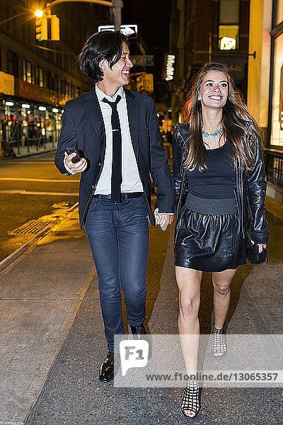Glückliches Paar hält sich an den Händen und geht auf der Straße