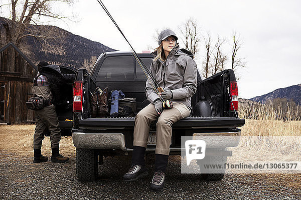 Woman holding fishing rod while sitting on pick-up truck