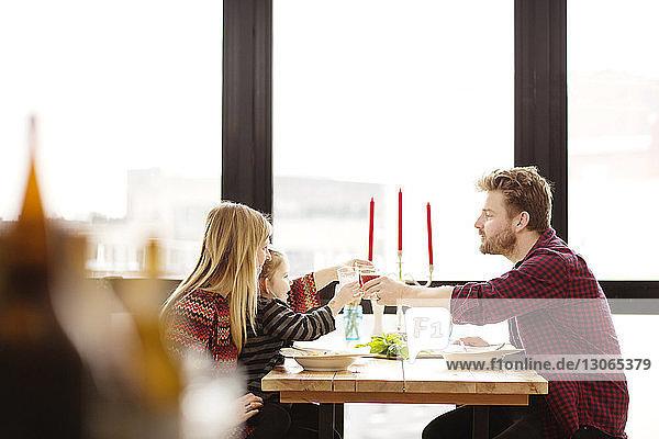 Familien  die zu Hause am Esstisch anstoßen