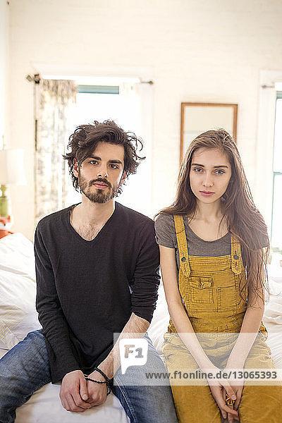 Porträt eines zu Hause auf dem Bett sitzenden Paares