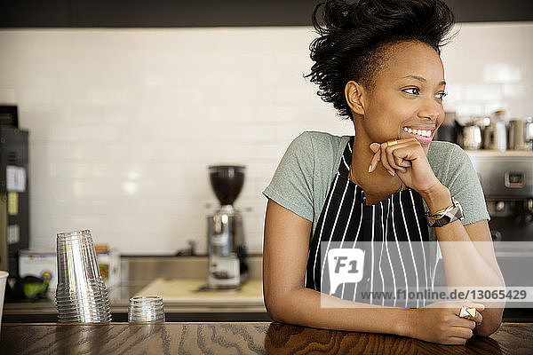 Happy woman looking away while standing at counter in cafe