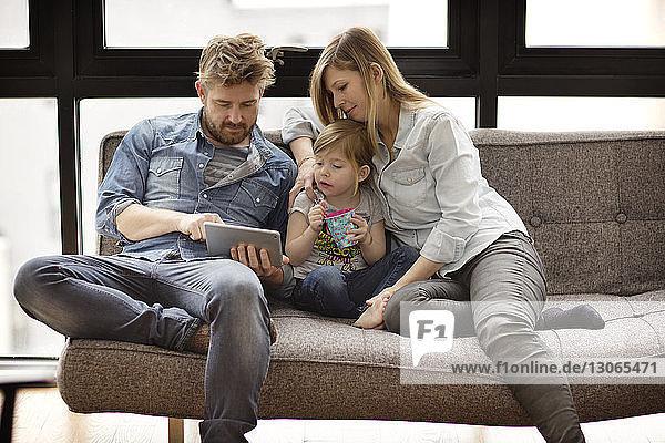 Familie schaut auf Laptop-Computer  während sie zu Hause auf dem Sofa sitzt