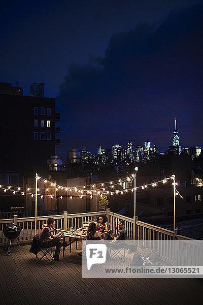 Hochwinkelansicht von Freunden  die nachts auf der Gebäudeterrasse sitzen
