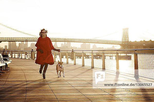 Frau rennt mit Hund auf der Promenade gegen die Williamsburg-Brücke