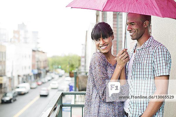 Lächelndes Paar mit Regenschirm auf dem Balkon stehend