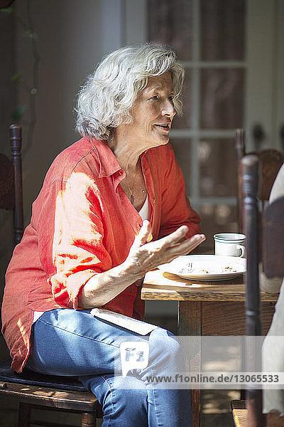 Frau frühstückt  während sie am Tisch sitzt