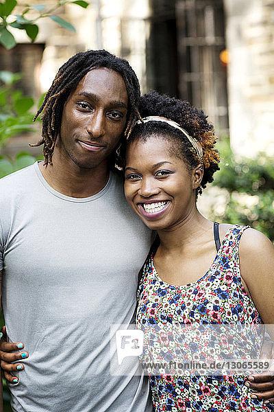 Porträt eines Paares  das sich gegen ein Gebäude stellt
