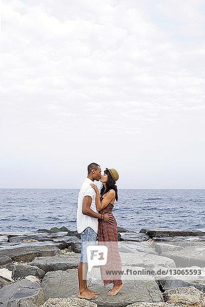 Seitenansicht eines Paares  das sich küsst  während es auf Felsen am Strand steht