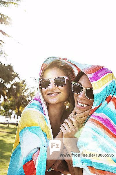 Glückliche  in ein Handtuch gewickelte Freunde stehen am klaren Himmel