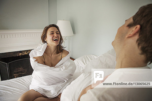 Happy woman wrapped in blanket sitting by man on bed at home