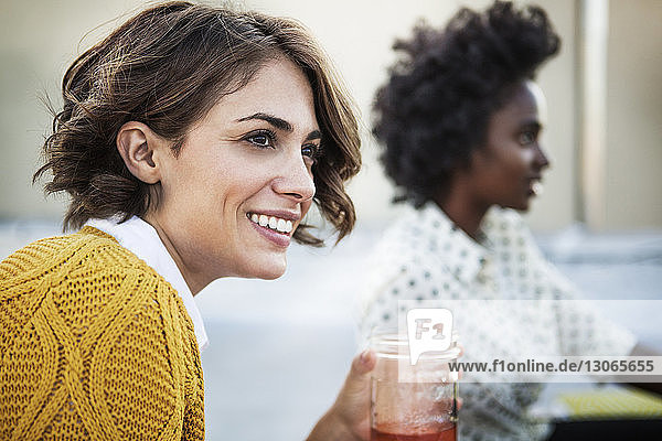 Smiling woman holding drinking glass with friend sitting in background