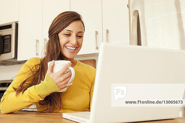 Frau hält Becher  während sie zu Hause einen Laptop benutzt