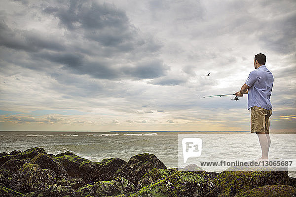 Man fishing while standing on rocks at beach