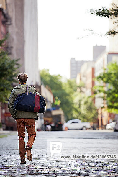 Rear view of man carrying bag while walking on street