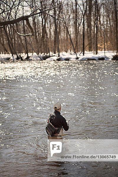 Rückansicht eines im See fischenden Mannes