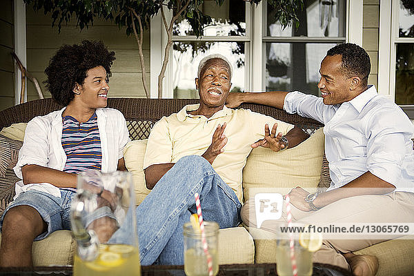 Happy multi-generation family talking while enjoying drinks in porch