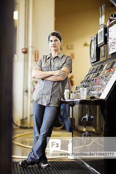 Portrait of female worker leaning on machinery at brewery