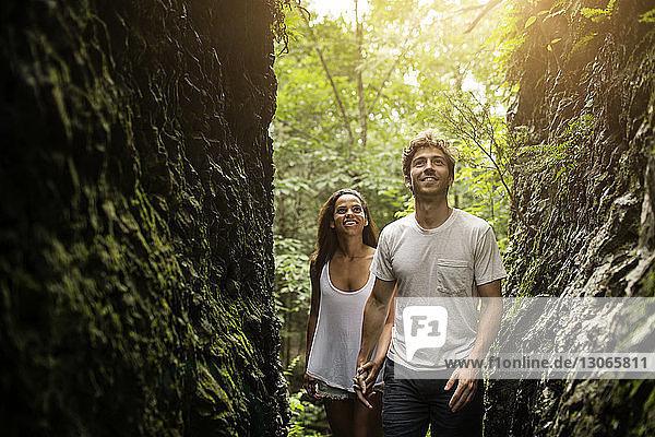 Ehepaar schaut auf  während es im Wald spazieren geht