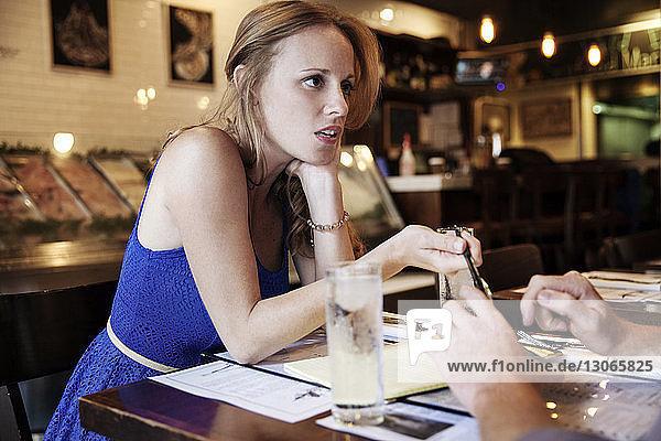 Frau unterhält sich mit Mann  während sie im Restaurant sitzt
