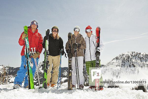 Porträt von Skifahrern  die auf schneebedecktem Feld vor klarem Himmel stehen
