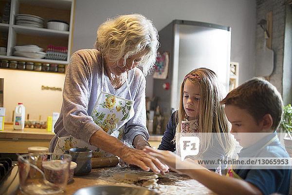 Children with grandmother preparing food in kitchen