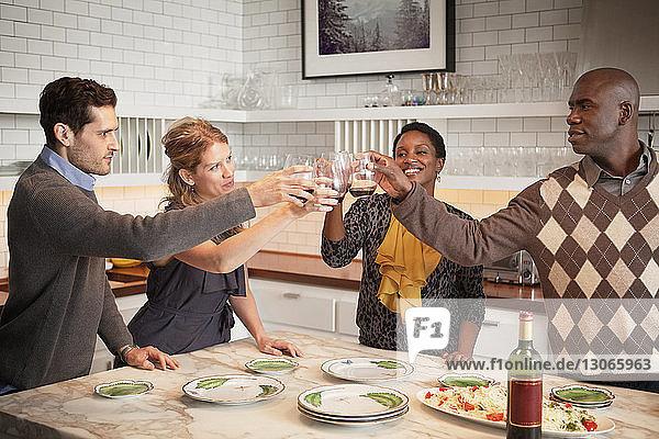 Glückliche Freunde stoßen am Tisch stehend auf Weingläser an