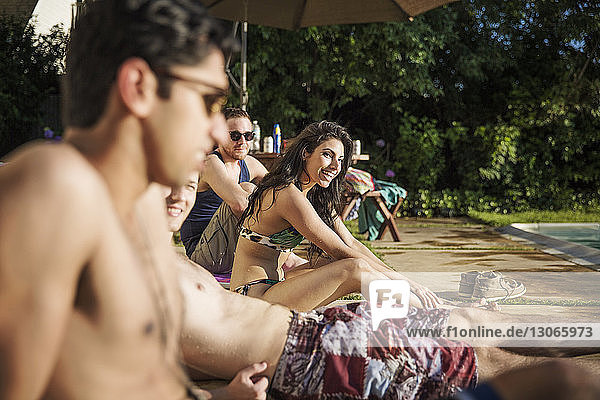 Happy friends relaxing at poolside