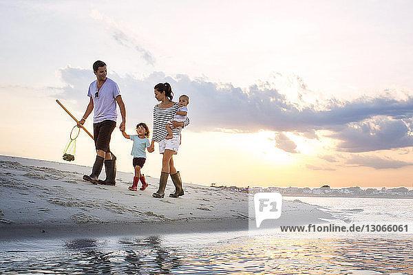 Eine Familie in voller Länge geht bei Sonnenuntergang am Meeresufer gegen den Himmel