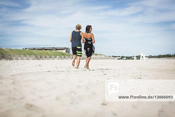 Rückansicht eines Paares  das auf Sand am Strand gegen den Himmel läuft