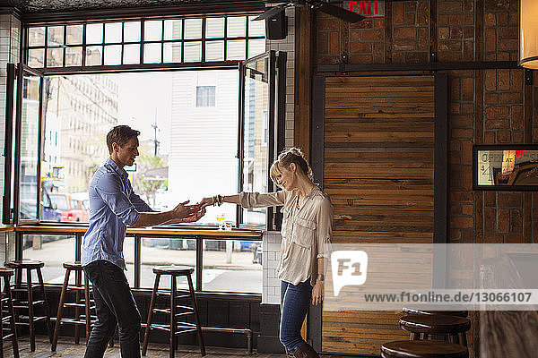 Man holding hand of woman while standing in bar