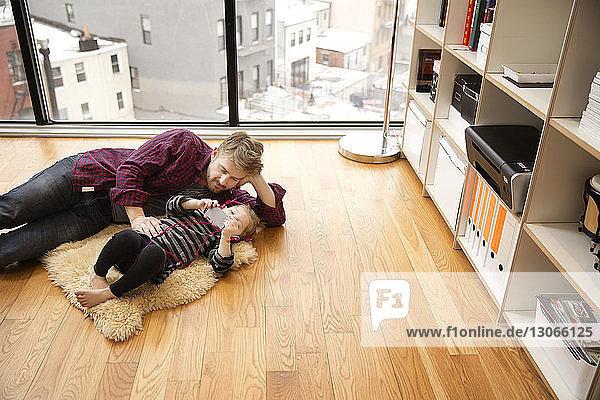 Hochwinkelansicht von Vater und Tochter  die zu Hause auf dem Boden liegen