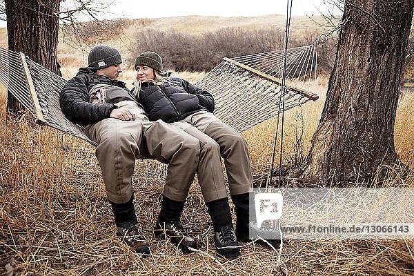Happy couple sitting on hammock