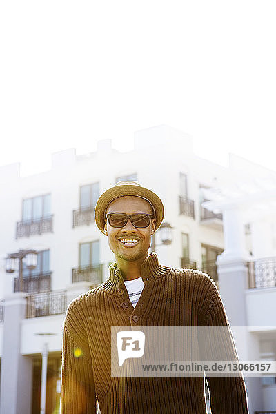 Porträt eines Mannes  der sich gegen Gebäude in der Stadt stellt