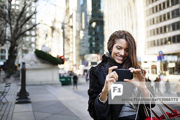 Frau fotografiert im Stehen auf einem Fußweg in der Stadt