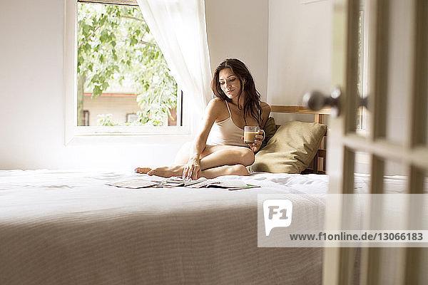 Frau mit Kaffeetasse liest Zeitschrift  während sie zu Hause auf dem Bett sitzt