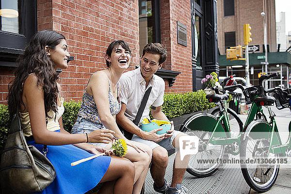 Fröhliche Freunde unterhalten sich im Straßencafé