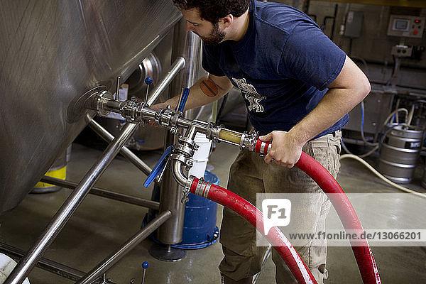 Hochwinkelaufnahme eines Mannes bei der Arbeit in einer Brauerei