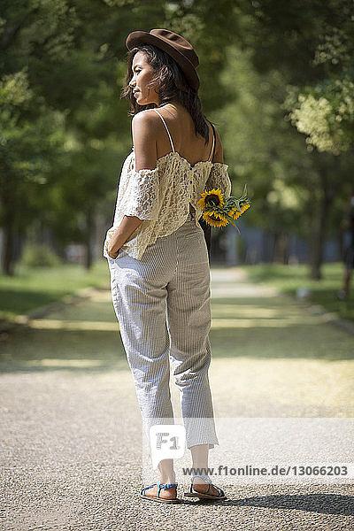 Nachdenkliche Frau hält Sonnenblumen und steht auf einem Fußweg im Park
